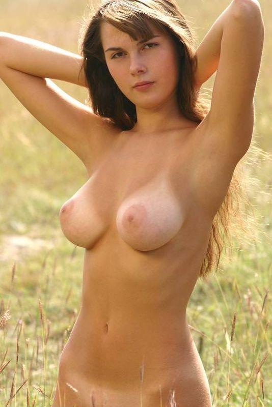 Голая грудастая брюнетка красиво позирует в поле - секс порно фото