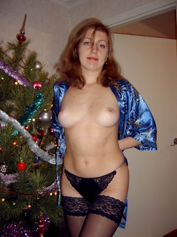 Сучка позирует на Рождество перед елкой - секс порно фото