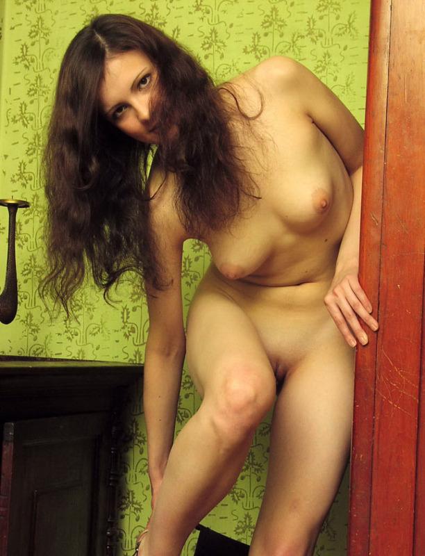 Брюнетка шустро лишает себя трусиков и всей одежды в комнате - секс порно фото